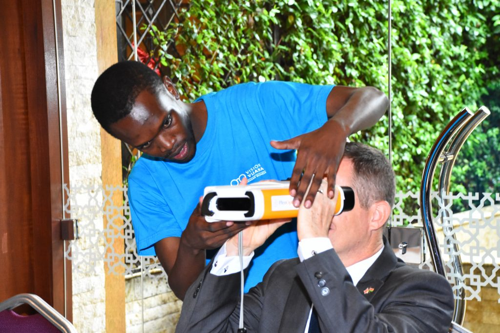 A man in a blue t-shirt is placing technology-goggles onto a man who is sitting down
