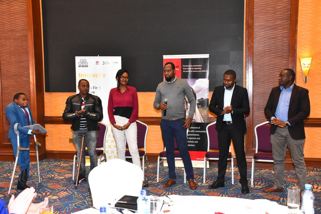 A group of innovators from cohort 1.0 stand in front of an audience